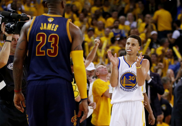 Stephen Curry of the Golden State Warriors celebrates a Game 1 victory while LeBron James of the Cleveland Cavaliers looks on.